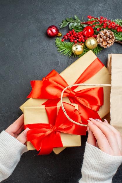 Vertikale ansicht der hand, die eine schöne geschenkbox aus einer tasche auf schwarzem hintergrund herausnimmt Kostenlose Fotos