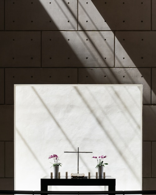 Vertikale ansicht der vasen und eines kreuzes auf einem tisch in einem raum mit betonwand Kostenlose Fotos