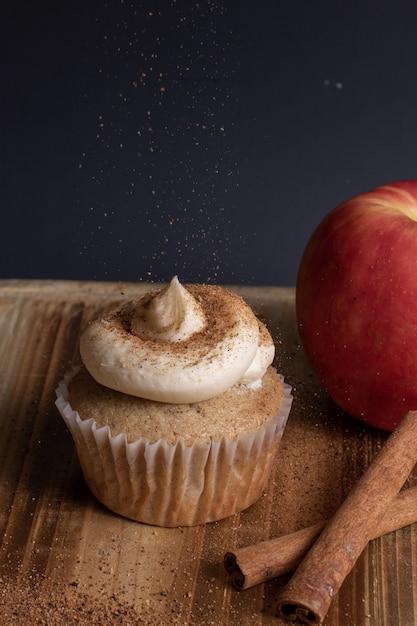Vertikale ansicht eines cupcakes mit zuckerguss, während ein kaffeepulver darüber gestreut wird Kostenlose Fotos