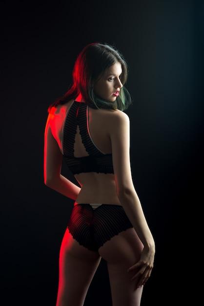 Vertikale ansicht foto schöne schüchterne dame in spitze bikini boudoir bh höschen. zarte dünne schlanke form isolierte schwarze wand Premium Fotos