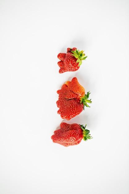 Vertikale ansicht von drei hässlich geformten erdbeeren auf dem weißen hintergrund Premium Fotos