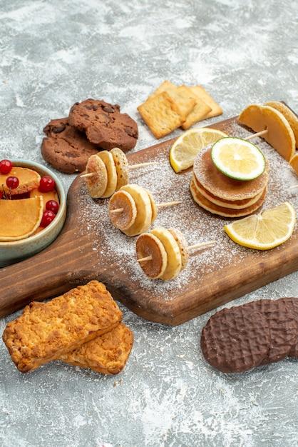 Vertikale ansicht von einfachen pfannkuchen mit zitronen auf schneidebrett und kekshonig auf blau Kostenlose Fotos