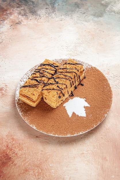 Vertikale ansicht von leckeren desserts, die mit schokoladensyrop für eine person auf buntem tisch verziert werden Kostenlose Fotos