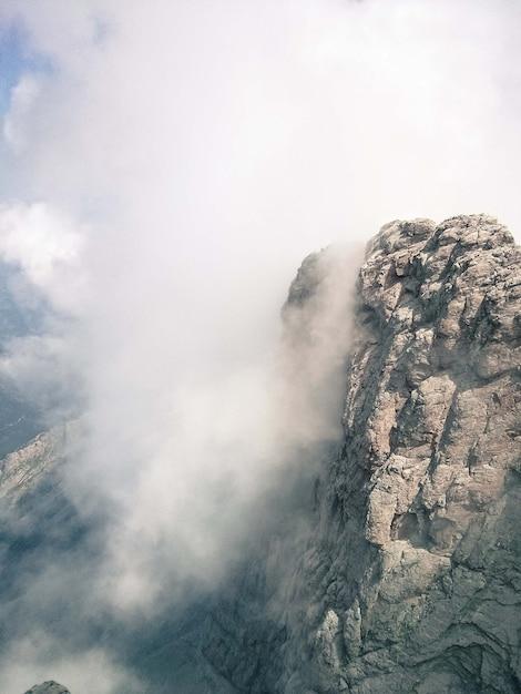 Vertikale aufnahme der klippe an einem nebligen tag - perfekt für hintergrund Kostenlose Fotos