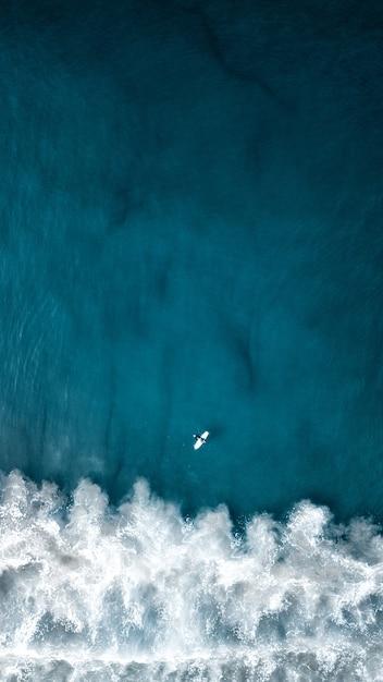 Vertikale aufnahme der luft über kopf von schönen ozeanwellen mit einem flugzeug, das oben fliegt Kostenlose Fotos
