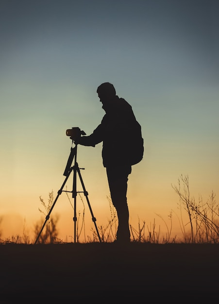 Vertikale aufnahme der silhouette eines mannes vor der kamera Kostenlose Fotos
