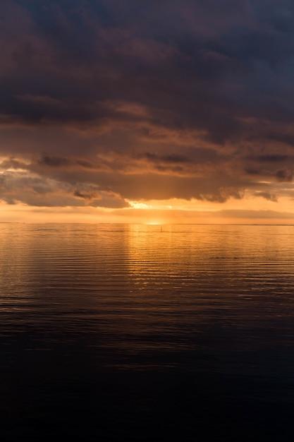 Vertikale aufnahme des atemberaubenden sonnenuntergangs am bewölkten himmel über dem ozean Kostenlose Fotos
