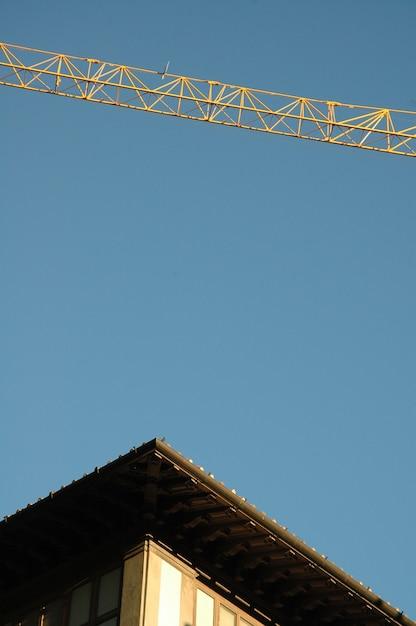 Vertikale aufnahme des daches eines gebäudes und eines krans mit klarem himmel Kostenlose Fotos