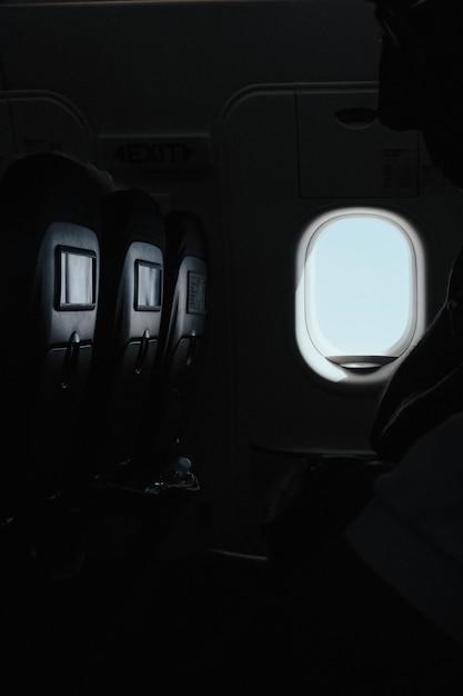 Vertikale aufnahme des fensters in einem flugzeug zum zeitpunkt des fluges Kostenlose Fotos