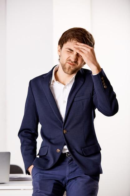Vertikale aufnahme des geschäftsmannes fühlen burnout, berühren stirn und schielen, leiden kopfschmerzen, schmerzhafte migräne im arbeitsbüro Kostenlose Fotos