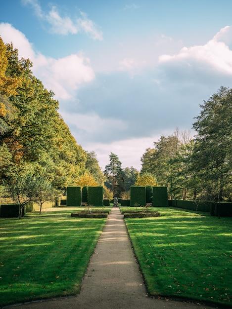 Vertikale aufnahme des hoetger-parks, der im grün unter einem bewölkten himmel im sonnenlicht in dortmund bedeckt ist Kostenlose Fotos