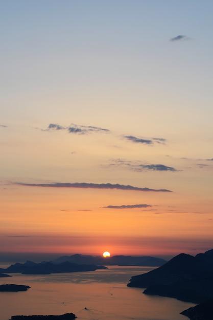 Vertikale aufnahme des horizonts mit wasser und sonnenuntergang in einem atemberaubenden blauen himmel Kostenlose Fotos