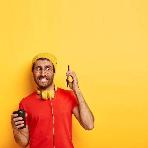 Vertikale aufnahme des verwirrten nervösen mannes vermeidet das sprechen auf dem smartphone Kostenlose Fotos