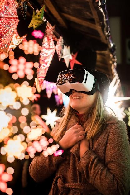 Vertikale aufnahme einer frau, die die imaginäre atmosphäre mit vr-brille genießt Kostenlose Fotos