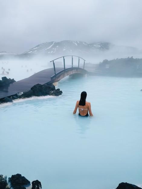 Vertikale aufnahme einer frau, die in einem heißen pool nahe der brücke schwimmt Kostenlose Fotos