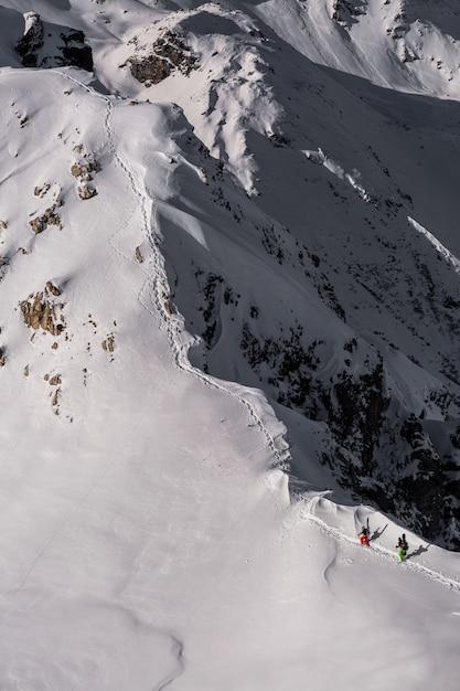 Vertikale aufnahme einer gebirgslandschaft, die in schönem weißem schnee in sainte foy, französische alpen bedeckt wird Kostenlose Fotos