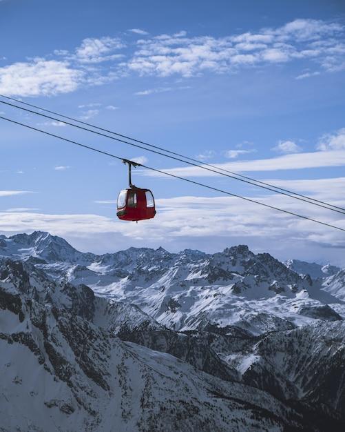 Vertikale aufnahme einer hütte der seilbahn über den bergen Kostenlose Fotos