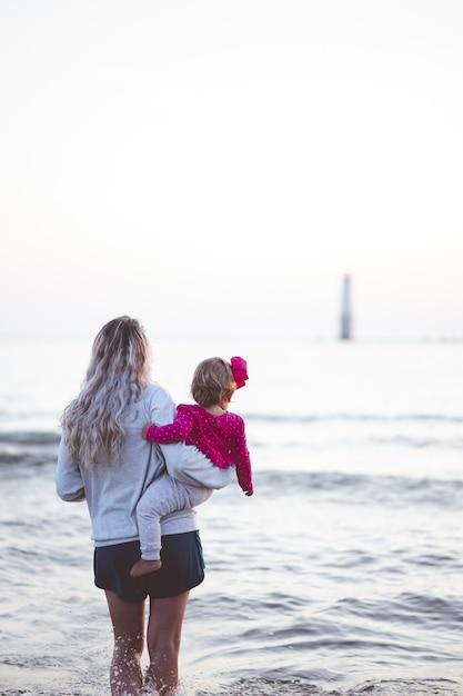 Vertikale aufnahme einer mutter, die ihr baby hält und den seehorizont betrachtet Kostenlose Fotos