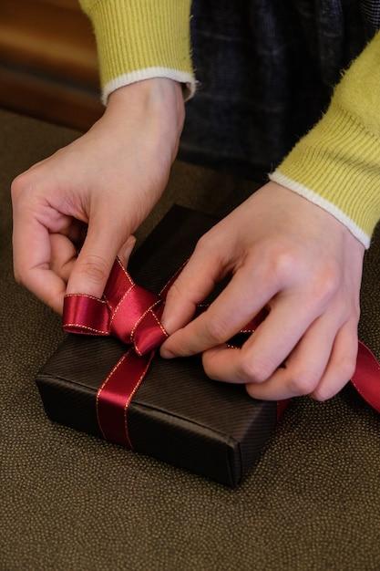 Vertikale aufnahme einer person, die ein geschenk mit einem niedlichen roten band einwickelt Kostenlose Fotos