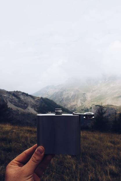 Vertikale aufnahme einer person, die eine metallflasche mit einem berg und bewölktem himmel hält Kostenlose Fotos