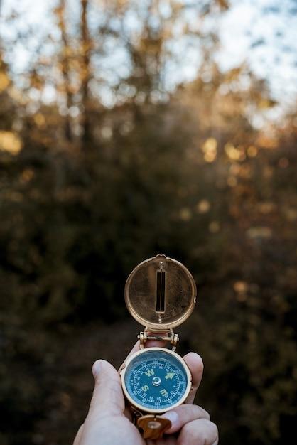 Vertikale aufnahme einer person, die einen kompass mit einem unscharfen natürlichen hintergrund hält Kostenlose Fotos