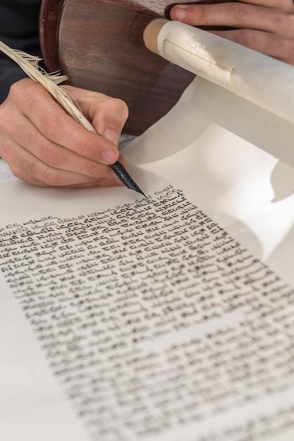 Vertikale aufnahme einer person, die mit einer feder auf einer schriftrolle schreibt Kostenlose Fotos