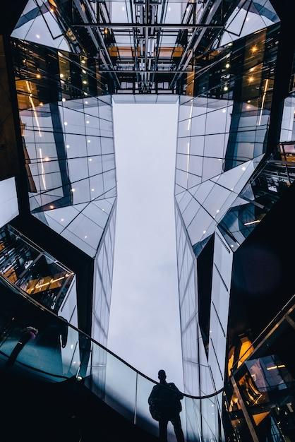 Vertikale aufnahme einer person, die zwischen den wolkenkratzern steht Kostenlose Fotos
