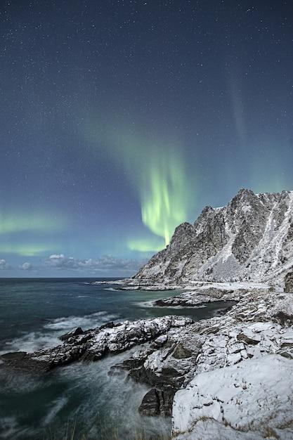 Vertikale aufnahme einer schönen schneebedeckten klippe am meer mit den nordlichtern am himmel Kostenlose Fotos