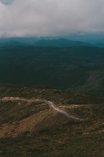 Vertikale aufnahme einer straße bis zum berg unter einem bewölkten himmel Kostenlose Fotos
