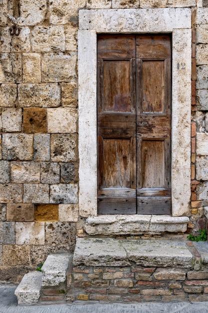 Vertikale aufnahme eines eingangs des historischen gebäudes von san gimignano in der toskana, florenz Kostenlose Fotos