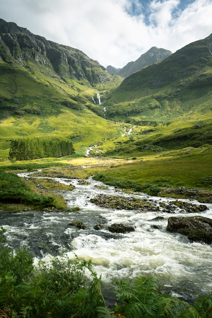 Vertikale aufnahme eines flusses, umgeben von den bergen und wiesen in schottland Kostenlose Fotos