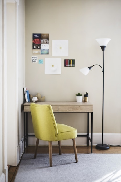 Vertikale aufnahme eines gelben stuhls und einer hohen lampe nahe einem holztisch mit büchern und pflanzentöpfen darauf Kostenlose Fotos