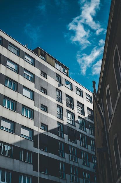 Vertikale aufnahme eines grauen und weißen gebäudes mit fenstern unter einem blauen himmel Kostenlose Fotos