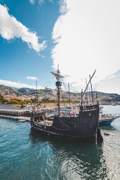 Vertikale aufnahme eines hölzernen schiffes auf dem wasser nahe dem dock in funchal, madeira, portugal. Kostenlose Fotos