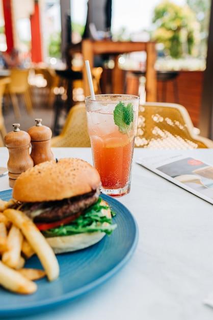 Vertikale aufnahme eines köstlichen burgers und einiger pommes frites und eines glases cocktail auf einem tisch Kostenlose Fotos