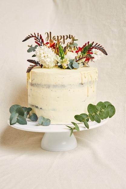 Vertikale aufnahme eines köstlichen geburtstags weiße cremeblumen auf dem oberen kuchen mit einem tropfen auf der seite Kostenlose Fotos