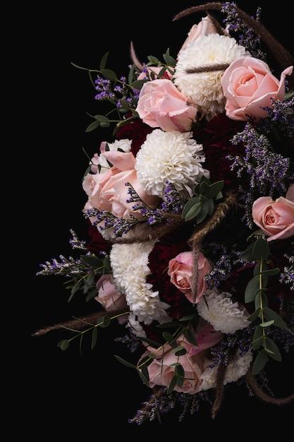 Vertikale aufnahme eines luxuriösen straußes von rosa und roten rosen und weißen dahlien auf einem schwarzen hintergrund Kostenlose Fotos