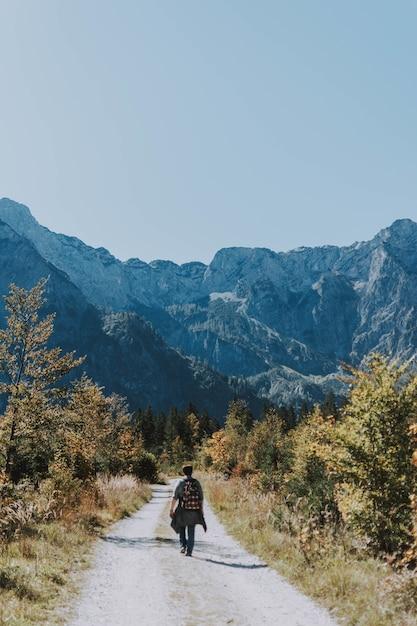 Vertikale aufnahme eines männlichen wanderers, der sich durch eine schmale schotterstraße in richtung felsiger berge wagt Kostenlose Fotos