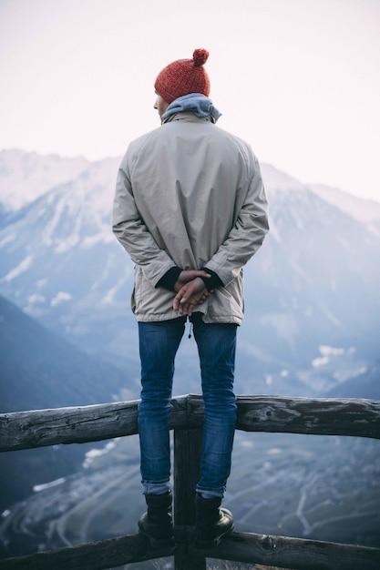 Vertikale aufnahme eines mannes, der einen roten hut trägt und auf einem holzzaun mit bergen steht Kostenlose Fotos