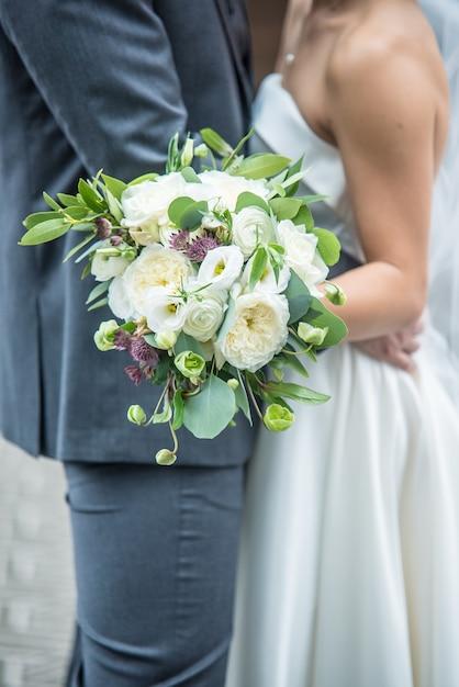 Vertikale aufnahme eines romantischen bräutigams und einer braut, die einen brautstrauß halten Kostenlose Fotos