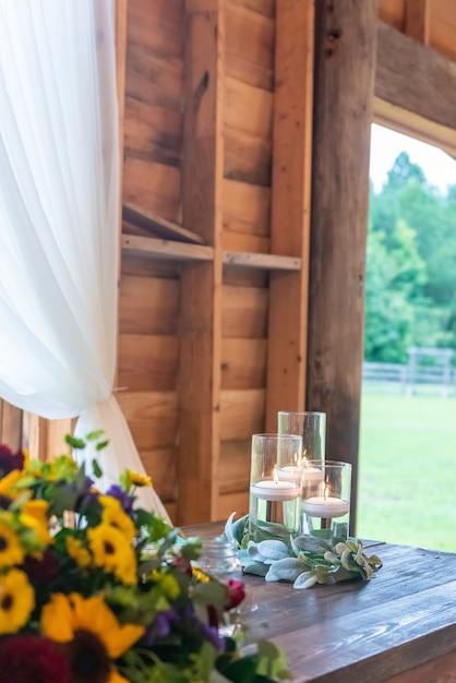 Vertikale aufnahme eines schönen hochzeitstischaufbaus mit kerzen und bunten blumendekoren Kostenlose Fotos