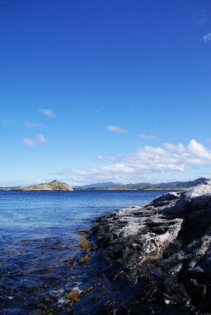 Vertikale aufnahme eines schönen sees, umgeben von klippen unter einem bewölkten himmel in norwegen Kostenlose Fotos