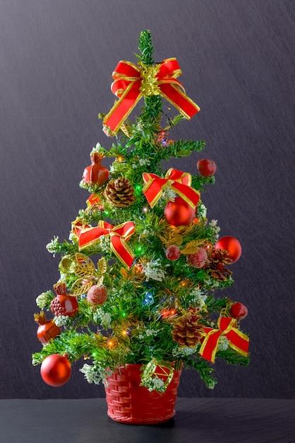 Vertikale aufnahme eines weihnachtsbaumes verziert mit roten bändern und kugeln Kostenlose Fotos