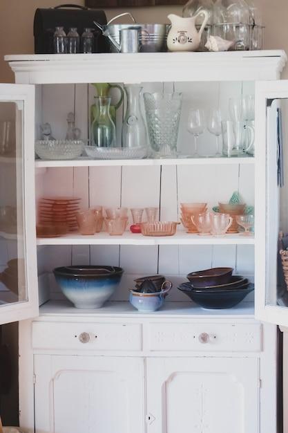 Vertikale aufnahme eines weißen regals mit verschiedenen arten von keramik- und glasküchengeschirr darin Kostenlose Fotos