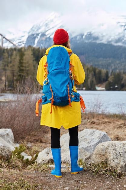 Vertikale aufnahme im freien von weiblichem touristen bewundert türkisfarbenes wasser vom see, steht nahe felsen, schaut auf schneeberge, atmet frische luft, trägt roten hut Kostenlose Fotos
