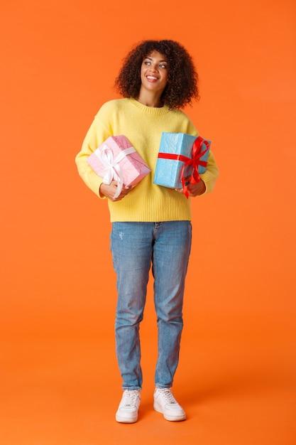 Vertikale aufnahme in voller länge verträumt und niedlich attraktive afroamerikanische frau, die sich umschaut, geschenke hält, orange wand. Kostenlose Fotos