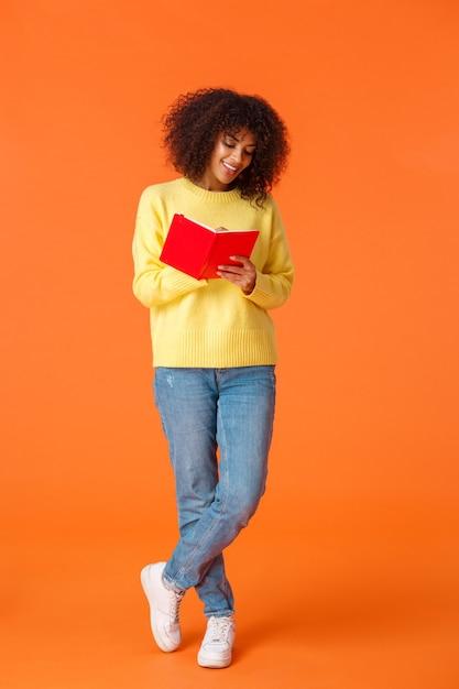 Vertikale aufnahme verträumte süße afroamerikanische studentin in voller länge mit afro-haarschnitt, freizeitkleidung, college-besuch, notizen machen, über orange wand stehen und lächelnd in notizbuch schreiben. Kostenlose Fotos