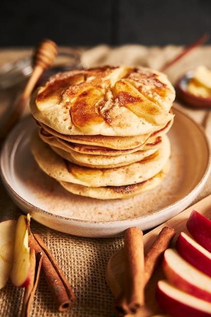 Vertikale aufnahme von apfelpfannkuchen auf einem teller mit apfelscheiben und zimt auf der seite Kostenlose Fotos