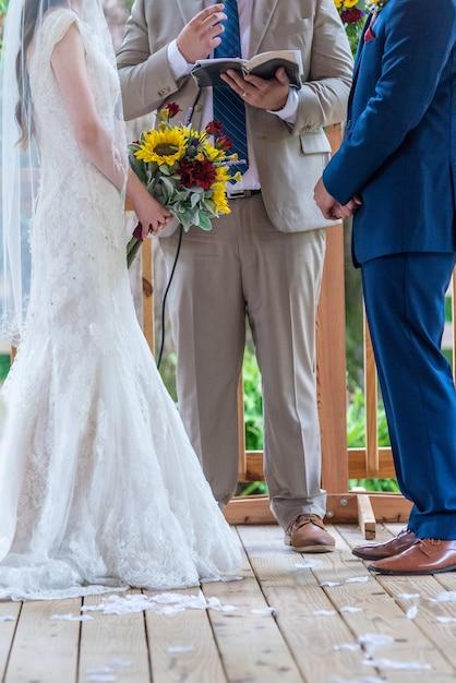 Vertikale aufnahme von braut und bräutigam, die während der hochzeitszeremonie voreinander stehen Kostenlose Fotos