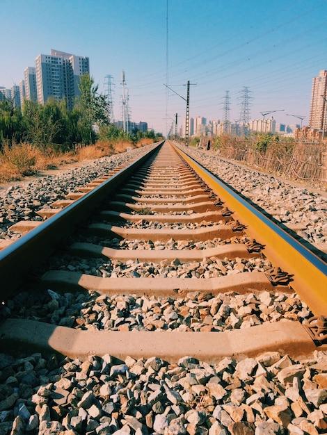 Vertikale aufnahme von eisenbahnschienen mit gebäuden Kostenlose Fotos